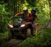 Man and woman driving a quadbike 4x4 motorbike on a dirt track course in the woods