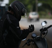 man on motorcycle wearing helmet and putting on gloves